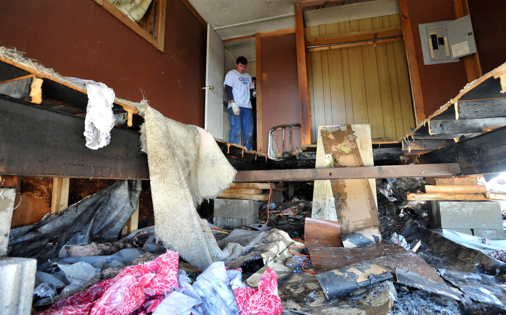 Starting over: Charlie Landry, 20, rummages through the bedroom after a fire destroyed his newly rented mobile home in Anson on Saturday. Landry and his girlfriend, Skyla Murray, were moving on Saturday when a frayed wire in the dryer sparked the fire.