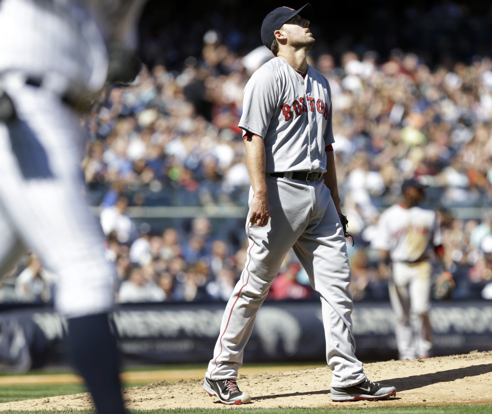 Boston Red Sox starting pitcher John Lackey reacts after New York Yankees' Alfonso Soriano hit a single during the sixth inning of a baseball game Saturday in New York.