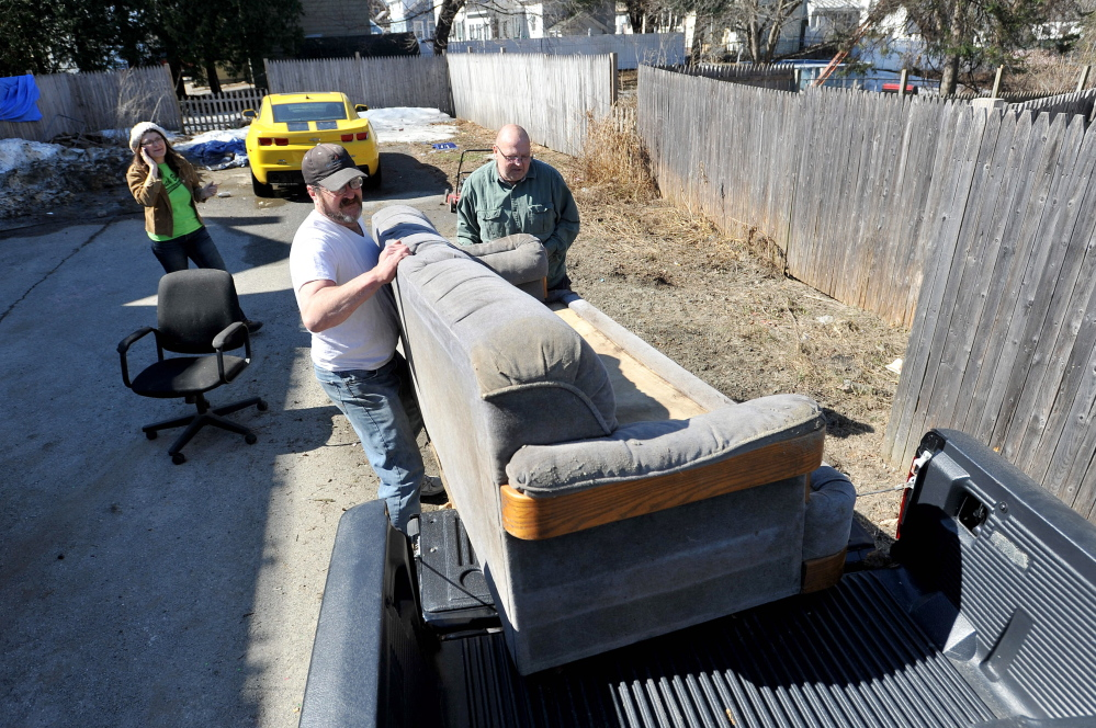 Sofa, so good: Chris Moody, 63, right, a volunteer with the South End Neighborhood Clean Up, gets help loading a couch into his truck Saturday from Chris Rancourt on Carey Lane in Waterville. The South End Clean Up, which happens once a year was created to help people who don't have the capacity or ability to have large items moved to the dump or donated to charity.