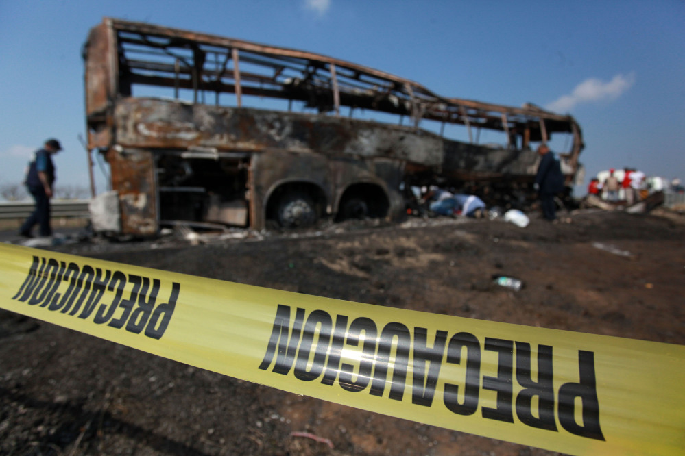 Caution tape creates a perimeter around a passenger bus that slammed into a broken-down truck and burst into flames near the town of Ciudad Isla in the Gulf state of Veracruz, Mexico, on Sunday.