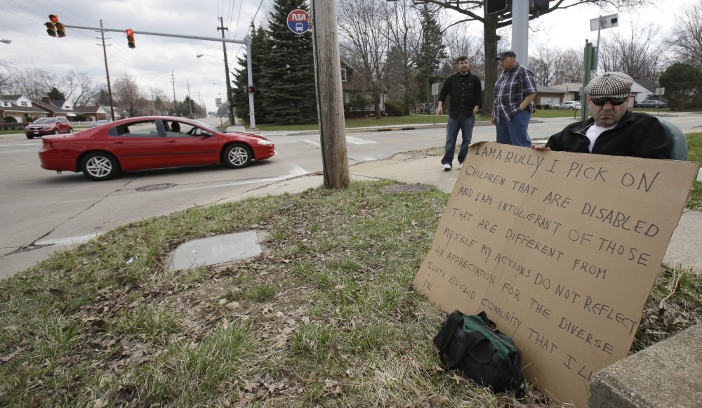 Edmond Aviv sits on a street corner holding a sign Sunday in South Euclid, Ohio, declaring he's a bully, a requirement of his sentence because he was accused of harassing a neighbor and her disabled children for the past 15 years.