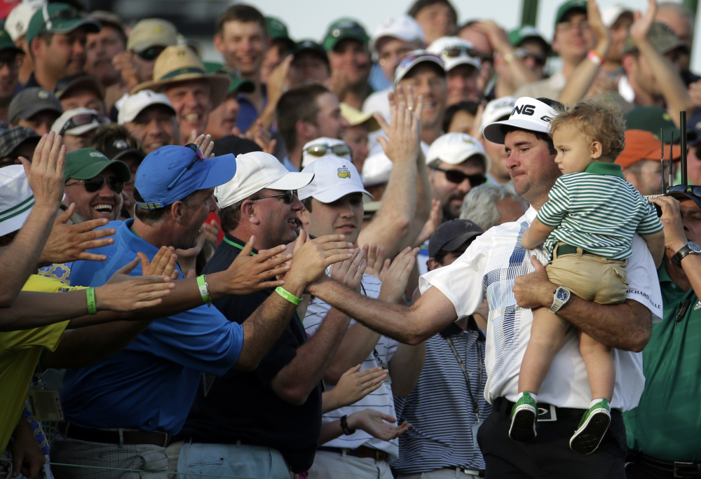 Bubba Watson, carrying his son Caleb, is congratulated by spectators after winning the Masters golf tournament Sunday in Augusta, Ga.