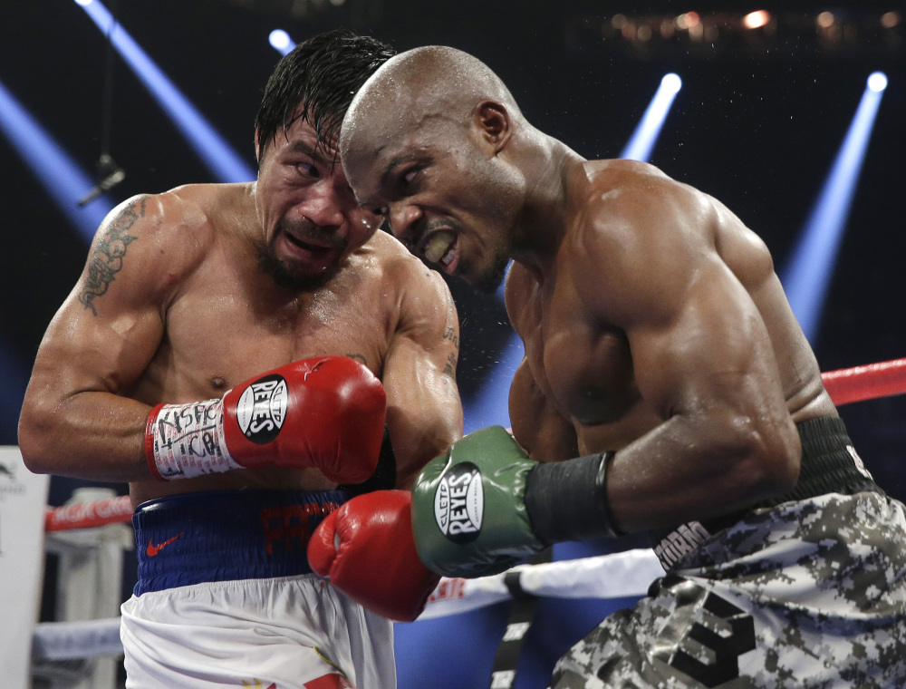 BACK ON TOP: Manny Pacquiao, left, trades blows with Timothy Bradley on Saturday in their WBO welterweight title fight in Las Vegas. Pacquiao won the bout by unanimous decision.