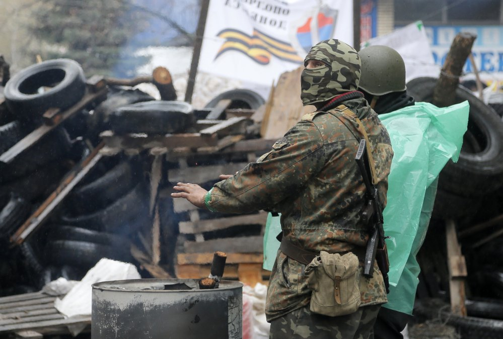 A pro-Russian gunman warms himself next to a bonfire as guards a seized police station in the eastern Ukrainian town of Slovyansk on Sunday. Ukrainian special forces exchanged gunfire with a pro-Russia militia in the eastern city Sunday, with at least one security officer killed and five others wounded.