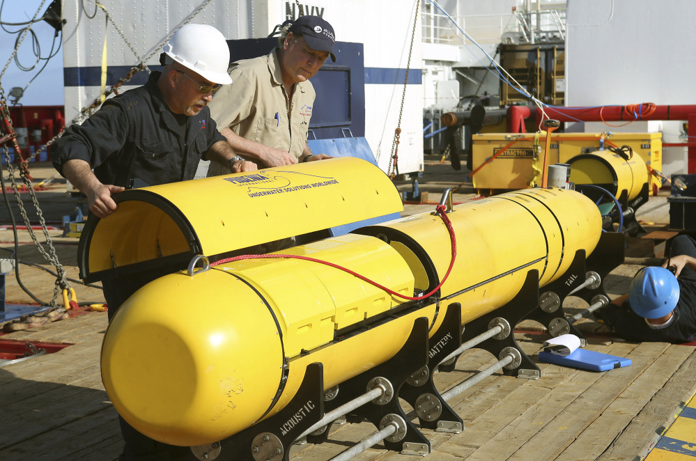 Australian Defense Force Phoenix International's Chris Minor, left, and Curt Newport inspect an autonomous underwater vehicle before it is deployed from ADV Ocean Shield in the search of the missing Malaysia Airlines Flight 370 in the southern Indian Ocean.