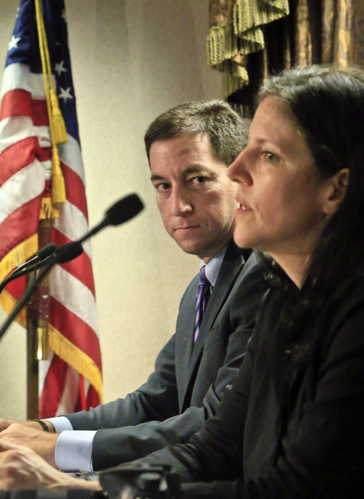 Journalist Glenn Greenwald, left, listens as Laura Poitras speaks earlier this month. The Washington Post and The Guardian won the Pulitzer Prize in public service Monday for revealing the U.S. government's sweeping surveillance efforts in stories based on secret documents handed over by National Security Agency leaker Edward Snowden. The reports were published by Barton Gellman of The Post and Greenwald, Poitras and Ewan MacAskill of The Guardian.