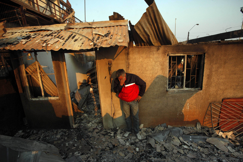 A man cries next to the remains of his house after a forest fire destroyed it in Valparaiso, Chile, Sunday.