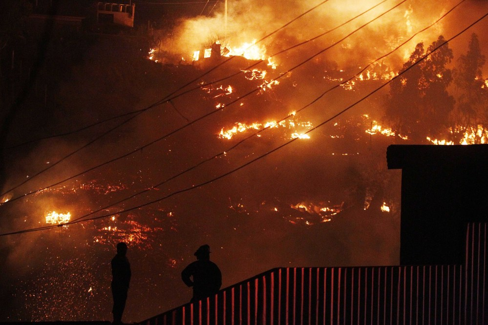 Emergency responders watch as an out-of-control fire destroys homes in the city of Valparaiso, Chile, Sunday. Firefighters struggled for a second night to contain blazes that reached this port city, killing at least a dozen people, destroyed hundreds homes and has forced the evacuation of thousands.