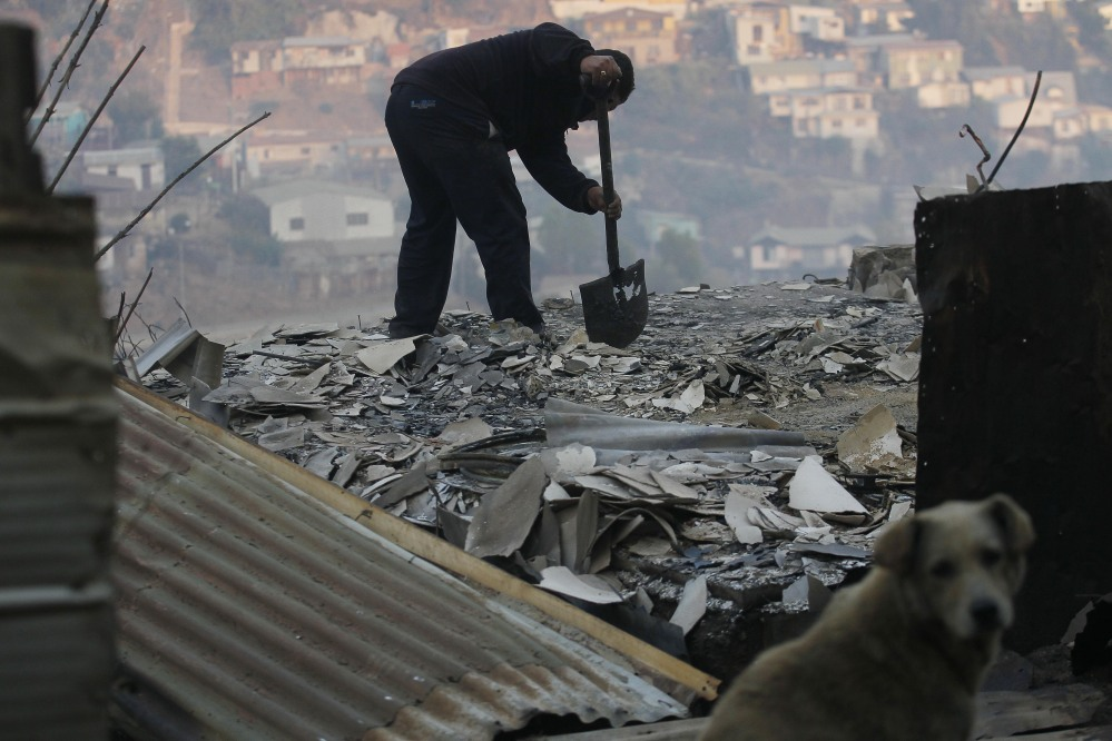 A man clears debris from his destroyed home after the forest fire reached urban areas in Valparaiso. The fires destroyed at least 2,000 houses by Sunday evening.