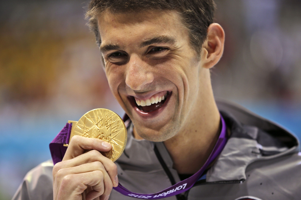 Michael Phelps displays his gold medal for the men's 100-meter butterfly swimming final at the 2012 Summer Olympics in London, in this Aug. 3, 2012, photo.
