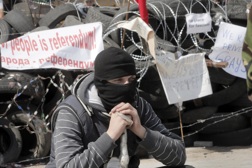 A masked pro-Russian activist guards a barricade at the regional administration building that they had seized earlier in Donetsk, Ukraine.