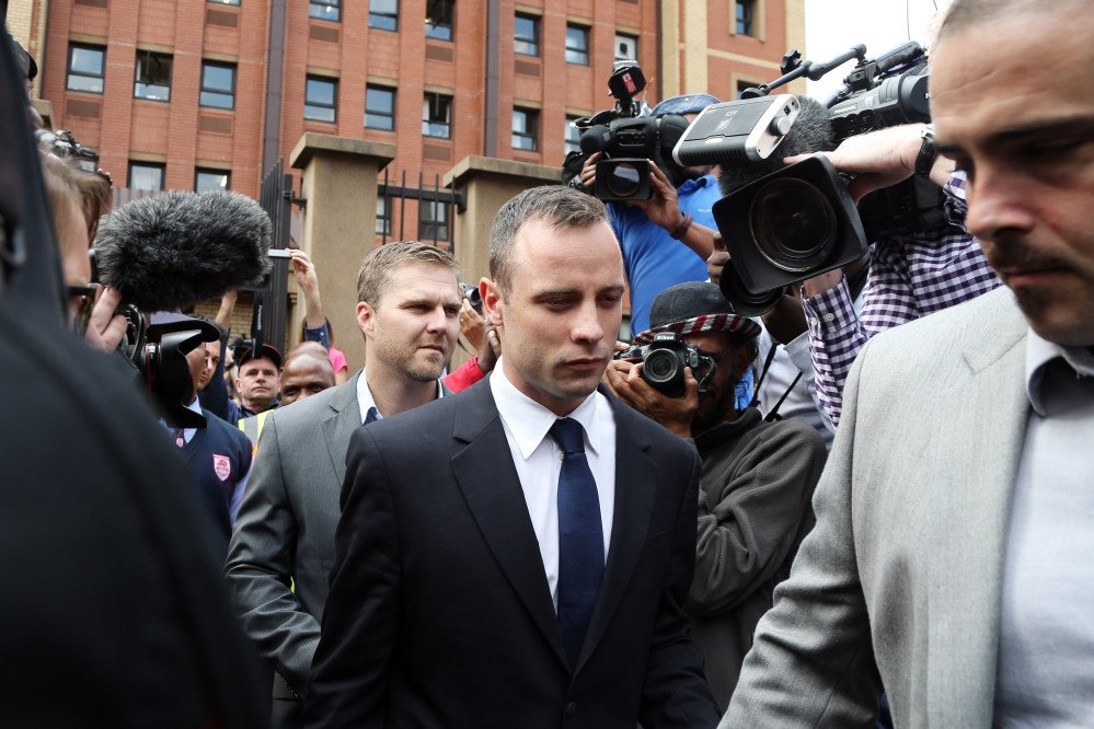 Oscar Pistorius, center, leaves the high court in Pretoria, South Africa, Tuesday. He is charged with murder for the shooting death of his girlfriend, Reeva Steenkamp, on Valentines Day in 2013.