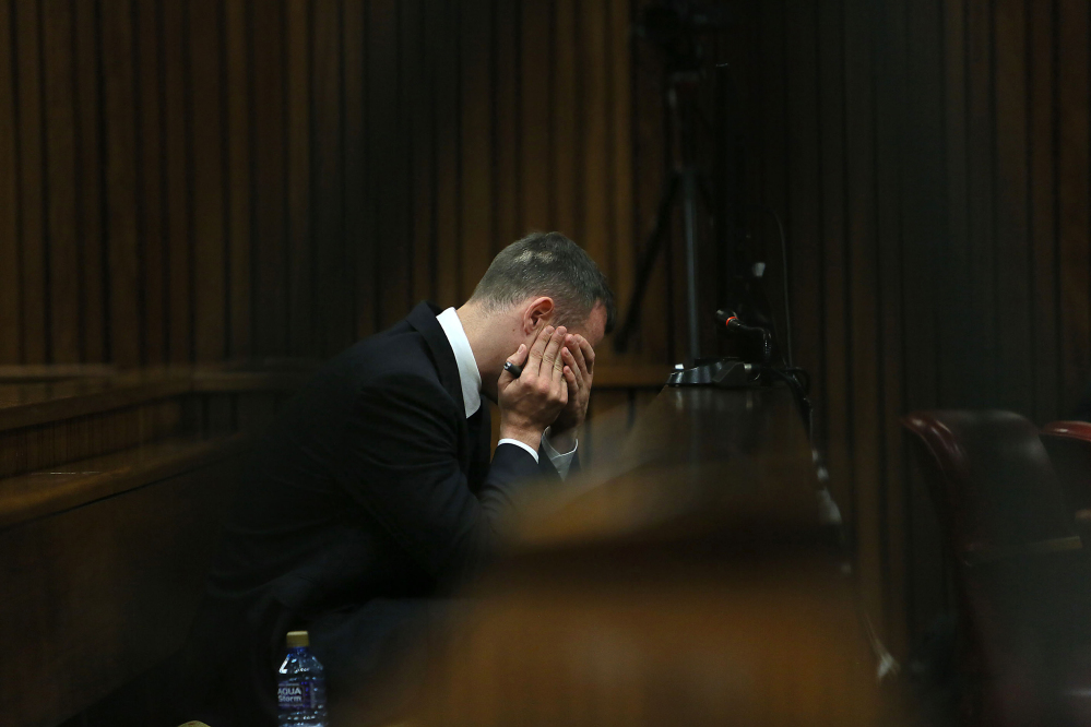 Oscar Pistorius holds his hands to his face as he listens to evidence being given in court in Pretoria, South Africa, Tuesday, after questioning by state prosecutor Gerrie Nel, had earlier finished.