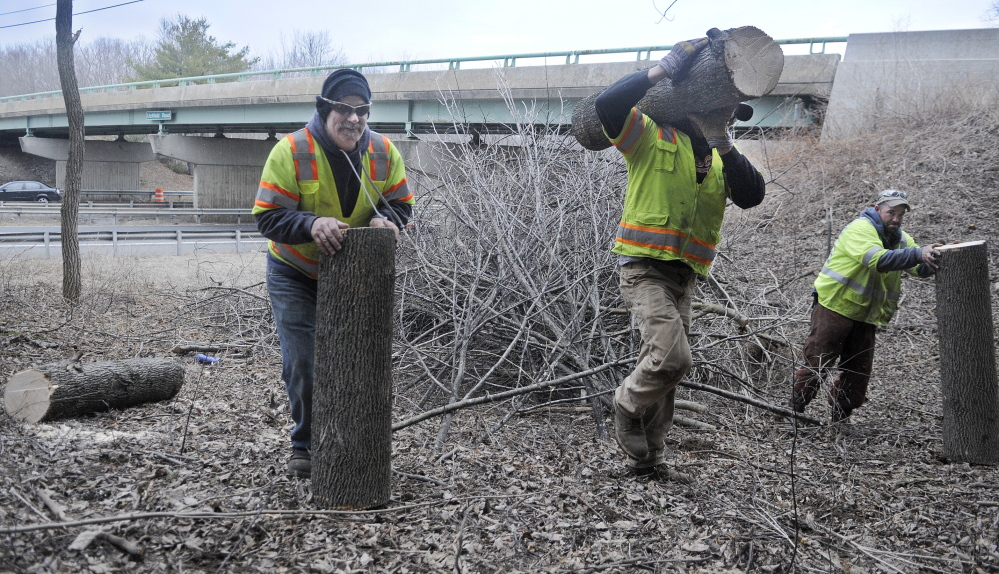 PROJECT PREPARATION: Wyman and Simpson General Contractors employees Eric Nichols, left, Brett Ulmer and Eric Levesque collect trees that were felled Tuesday to make way for the company to undertake a construction project on the bridge spanning the Maine Turnpike on Litchfield Road.
