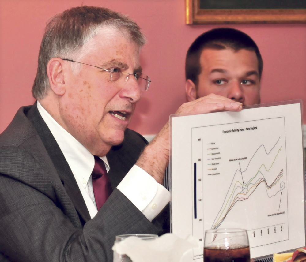 ECONOMY: Independent gubernatorial candidate Eliot Cutler displays a graph that illustrates Maine's lack of economic growth during a campaign stop Tuesday in Skowhegan. At right is Skowhegan Rotary Club member Reid Gibson.