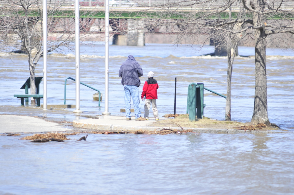 THIS PARK COULD HOLD AN ARK: People look at the rising Kennebec River beside the Augusta Waterfront Park sign on Wednesday in downtown Augusta. The river was at 16 feet around 2 p.m. and predicted to rise another few feet later in the evening.