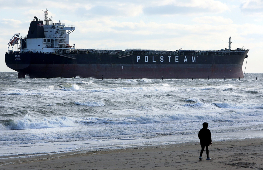 A person walks along the beach Wednesday near where the 751-foot bulk carrier Ornak ran aground Tuesday night in the lower Chesapeake Bay near First Landing State Park, in Virginia Beach, Va. There were no reports of injuries, damage or pollution from the grounding, and the vessel was not blocking other water traffic, said Coast Guard spokesman Petty Officer First Class Brandyn Hill.