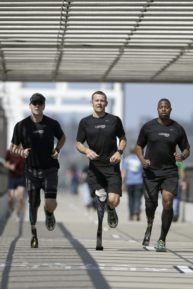 Amputee marathon runners Chris Madison, left, Jeff Glasbrenner, center, and Andre Slay train on a footbridge in Little Rock, Ark.