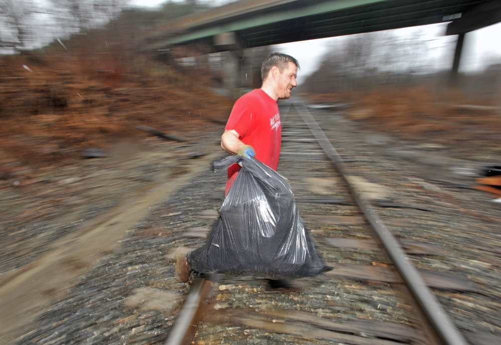 """CLEANING UP: Ward 4 Waterville City Councilor Erik Thomas cleans up trash under the County Road overpass Tuesday. Thomas, chairman of the city's solid waste committee, took the initiative to clean up illegally dumped trash. """"We need less complainers and more doers,"""" Thomas said. """"If you see something that needs to be done, do it."""""""