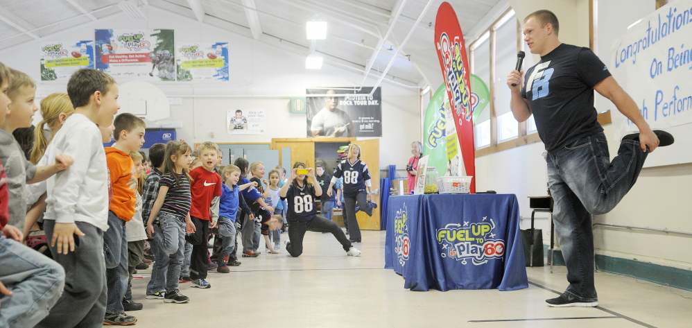 AN EXERCISE IN MOBILITY: National Football League player Matt Mulligan shows Pittston Consolidated School students a stretch Wednesday during a visit. His visit was a reward for the school's participation in Fuel Up to Play 60, the NFL's nutrition and fitness initiative.