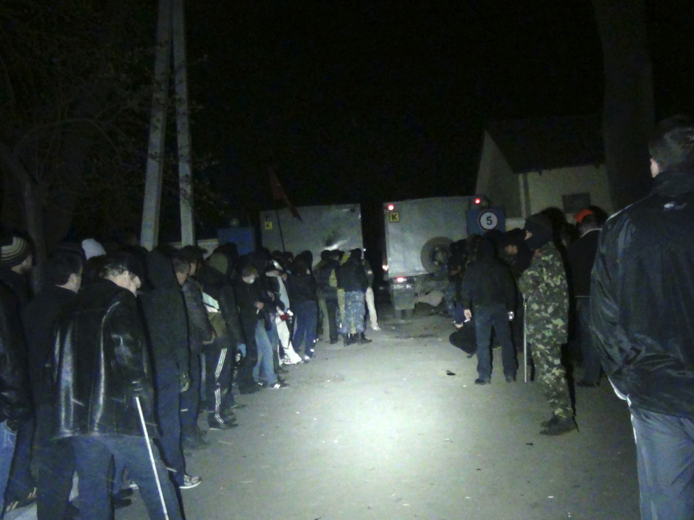 Unarmed pro-Russian militants line up at the gates to the National Guard base, blocked by trucks in Mariupol, early Thursday. Three pro-Russian militants died and 13 were wounded when Ukrainian troops repelled an attack on the National Guard base in the Black Sea port of Mariupol.
