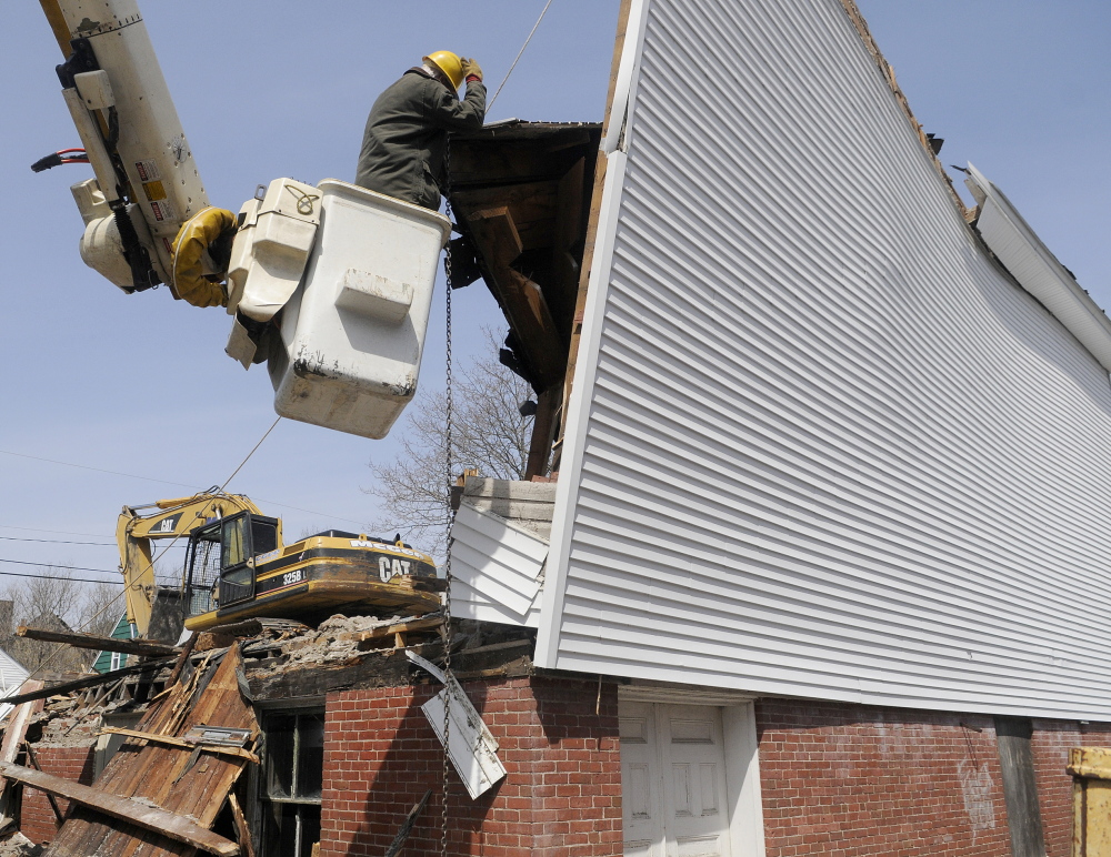 END OF AN ERA: Bob Doyle hooks a rope and chain Thursday to an exterior wall of the Masonic Lodge in Winthrop. The arborist and Mason volunteered his time to help raze the structure to make way for an expanded C.M. Bailey Public Library.