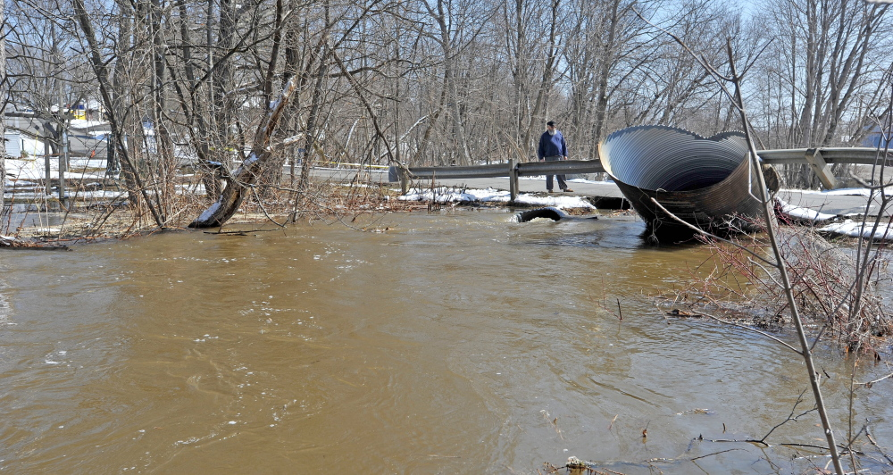 SWOLLEN STREAM: People stand on the road next to the swollen Sebasticook River East Branch on Wednesday as flooding closed Main Street in downtown Dexter.