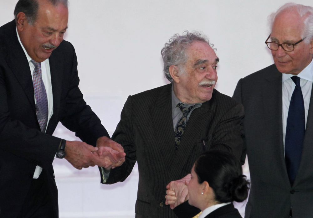 In this March 2011 file photo, Mexican telecom tycoon and world's richest man Carlos Slim, left, and British financier Sir Evelyn de Rothschild, right, help Nobel laureate Gabriel Garcia Marquez at the inauguration of the Soumaya Museum's new home in Mexico City. Marquez died Thursday April 17, 2014 at his home in Mexico City.