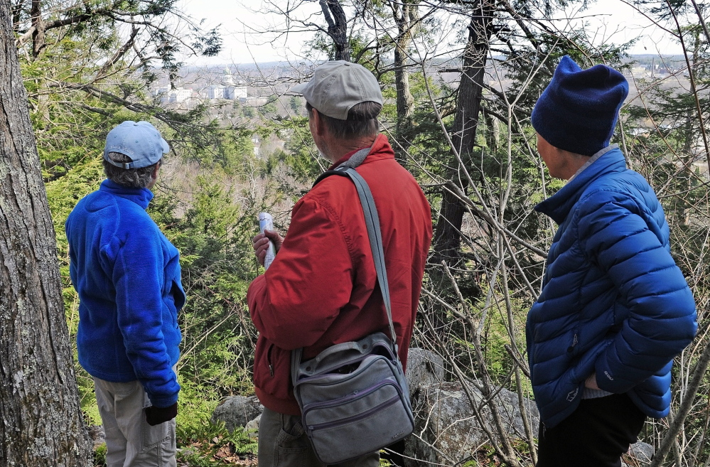 Hilltop view: City Councilor Dale McCormick, left, Brian Kent and Sue Bell look down from the summit onto the State House complex during a walking tour of Howard Hill on Friday in Augusta. The wooded hill is the backdrop to the State House.