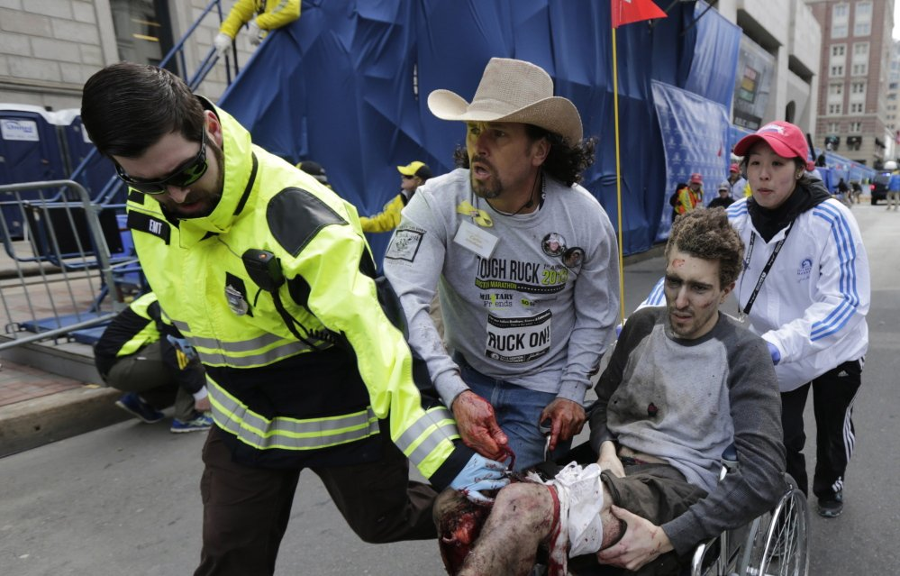 Carlos Arredondo, center, pushes Jeff Bauman in a wheelchair after Bauman was injured in the Boston Marathon bombings. Both Arredondo and his friend John Mixon of Ogunquit have been feted over the past year by Boston organizations grateful for their actions in the bombings' aftermath.