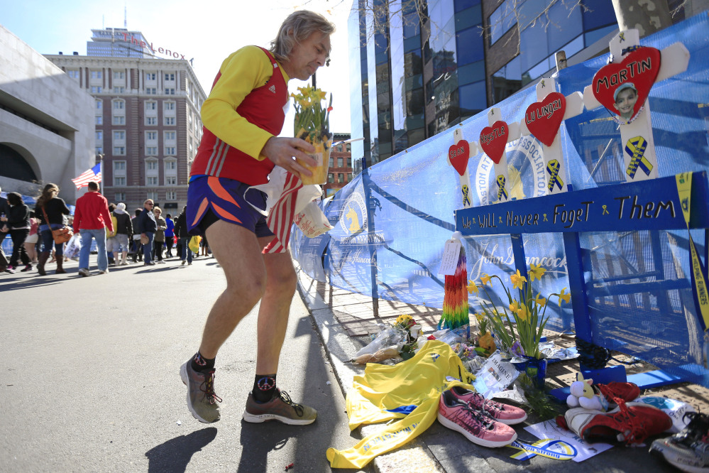 Memorial Runners: Ron McCracken, of Dallas, pays his respects at a makeshift memorial honoring to the victims of the 2013 Boston Marathon bombings ahead of Monday's 118th Boston Marathon, Sunday, in Boston. McCracken's race last year was cut short due to bombings and Monday's race will mark his 14th year running in the Boston Marathon. The memorial is where the first of two explosions happened last year near the finish line.