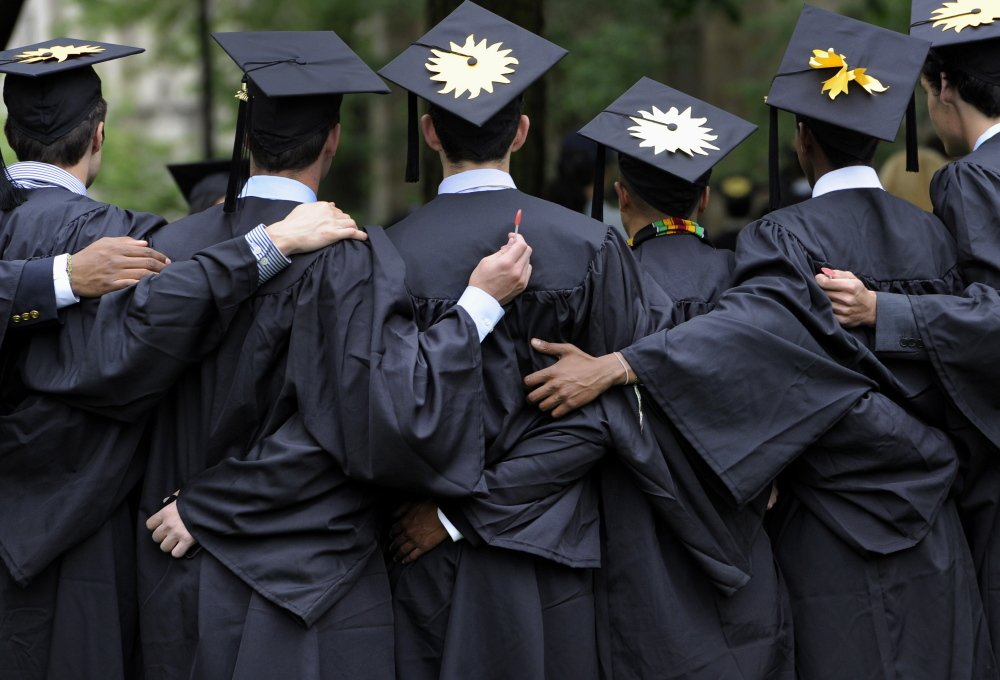 Graduates pose for photographs during commencement at Yale University in New Haven, Conn., in this May 20, 2013 photo. In a report last year, McKinsey & Company found that 41 percent of graduates from top universities could not land jobs in their chosen field after graduation.
