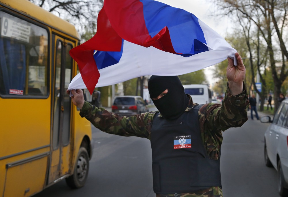 "A masked pro-Russia demonstrator waves the Russian flag in Donetsk, eastern Ukraine, on Tuesday. U.S. Vice President Joe Biden warned Russia on Tuesday that ""it's time to stop talking and start acting"" to reduce tension in Ukraine."