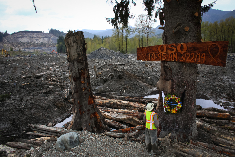 Ben Woodward looks up at a sign commemorating the moment of the Oso mudslide on Monday. The wooden memorial was attached to a towering spruce tree, one of the few in the debris field left standing after the disaster. Tuesday is the one month anniversary of the mudslide that killed a confirmed 41 people.