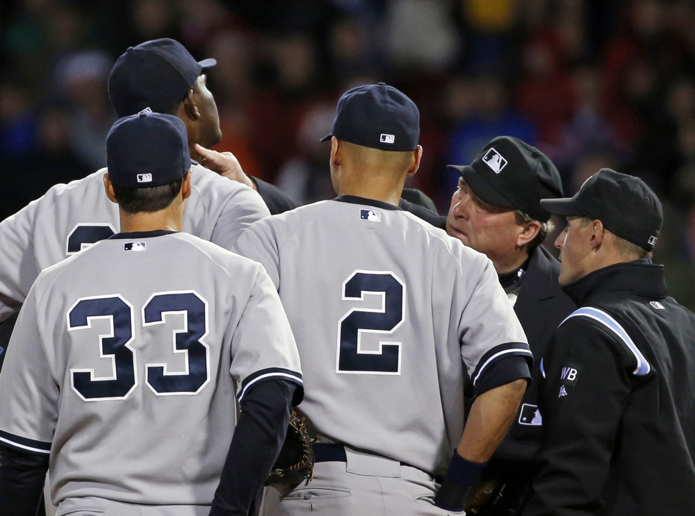 Home plate umpire Gerry Davis touches the neck of New York Yankees starting pitcher Michael Pineda in the second inning Wednesday. Pineda was ejected after umpires found with a foreign substance on his neck.