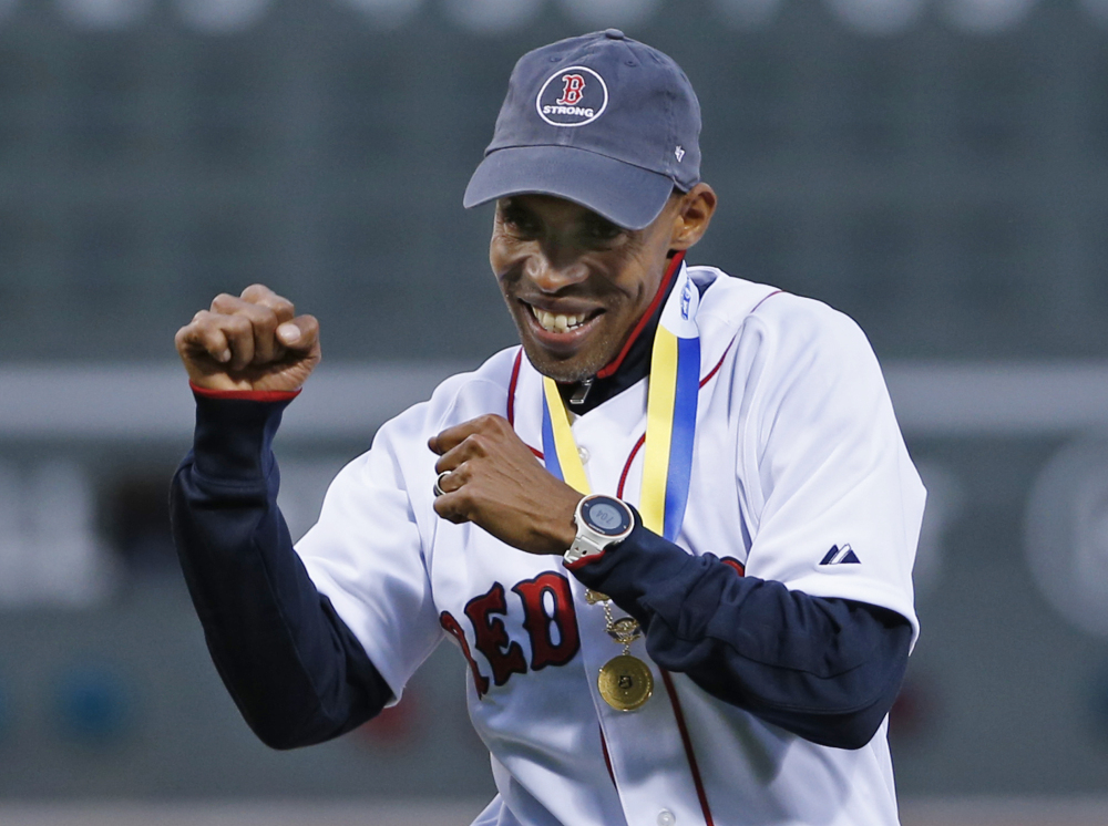 Meb Keflezighi, men's winner of this week's Boston Marathon, reacts after throwing the ceremonial first pitch at Fenway Park on Wednesday.