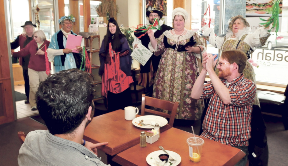 BRAVO: Sean Landry, right, of Pittsfield, claps as members of the Recycled Shakespeare company enter Selah Tea restaurant in Waterville during a celebration of Shakespeare's 450th birthday on Wednesday. Landry later read one of the Bard's sonnets.