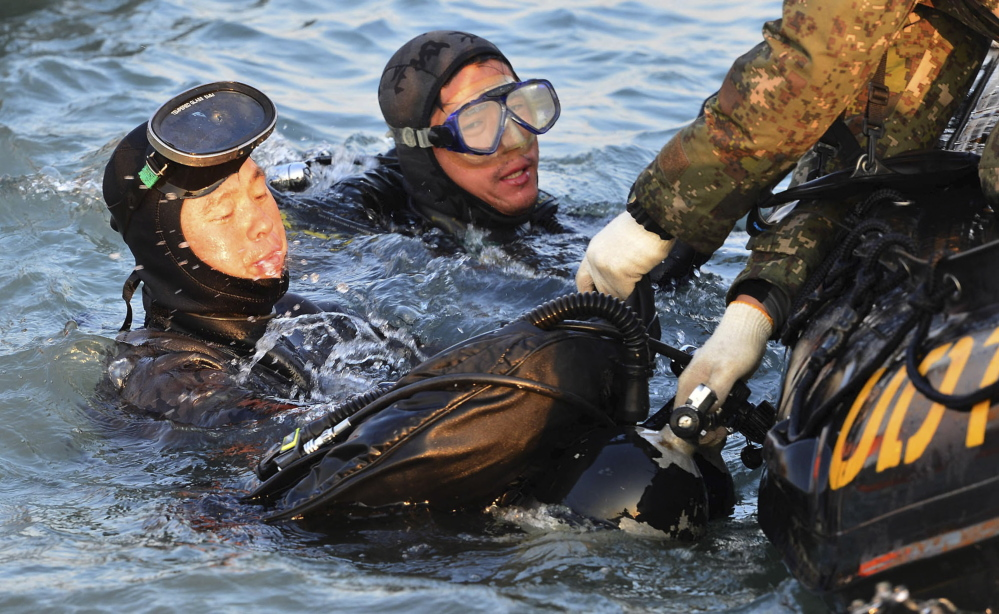 Divers look for people believed to have been trapped in the sunken ferry Sewol in the water off the southern coast near Jindo, South Korea. The grim work of recovering bodies from the ferry proceeded rapidly Wednesday, though a government official said divers must now rip through cabin walls to retrieve more victims.