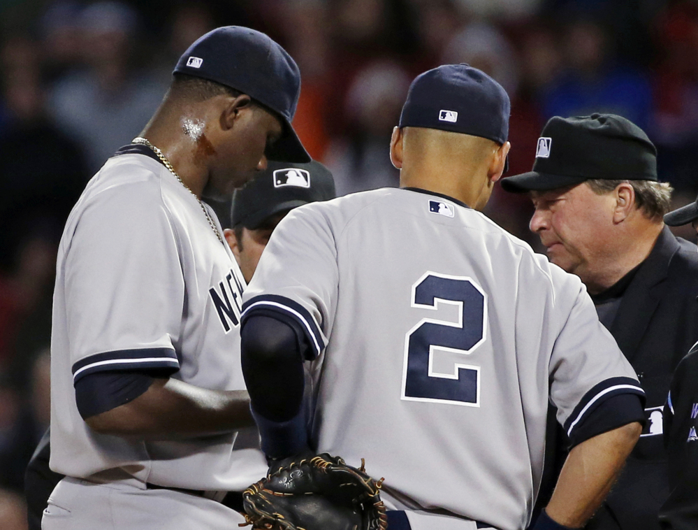 Home plate umpire Gerry Davis points to the neck of Yankees starting pitcher Michael Pineda, who admits he rubbed pine tar there to use during the game to get a better grip on the ball. Shortstop Derek Jeter (2) and others join them on the mound in the second inning Wednesday.
