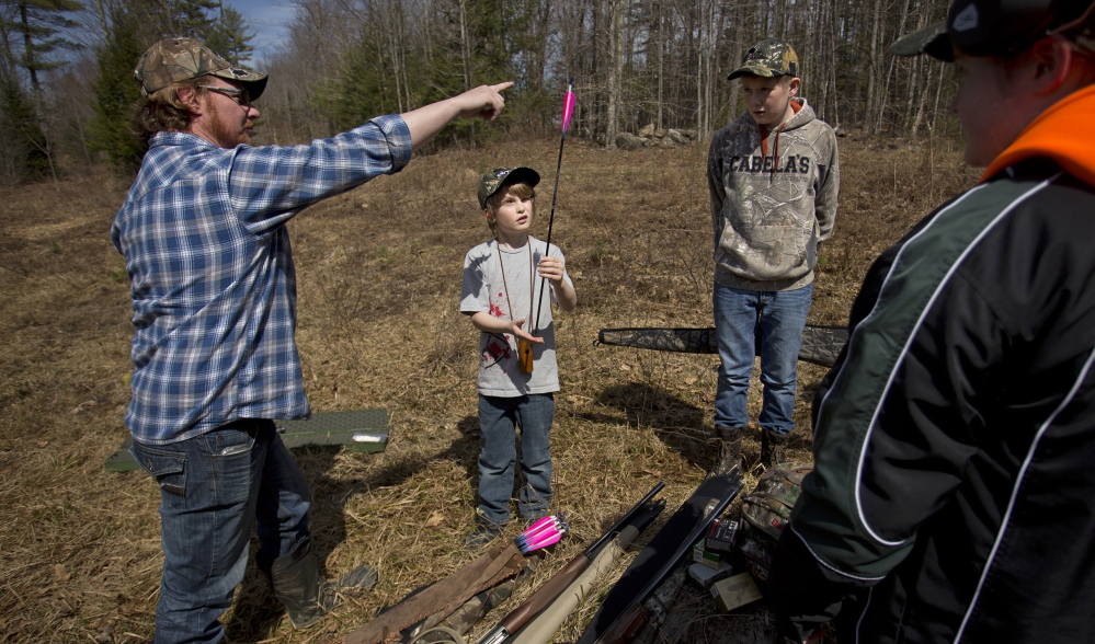Travis McLeod of Halifax, Nova Scotia, shows Brady Whitman, 9, of Halifax how to balance an arrow on his fingertip during a youth turkey-hunting camp held at Point Sebago Resort in Casco.