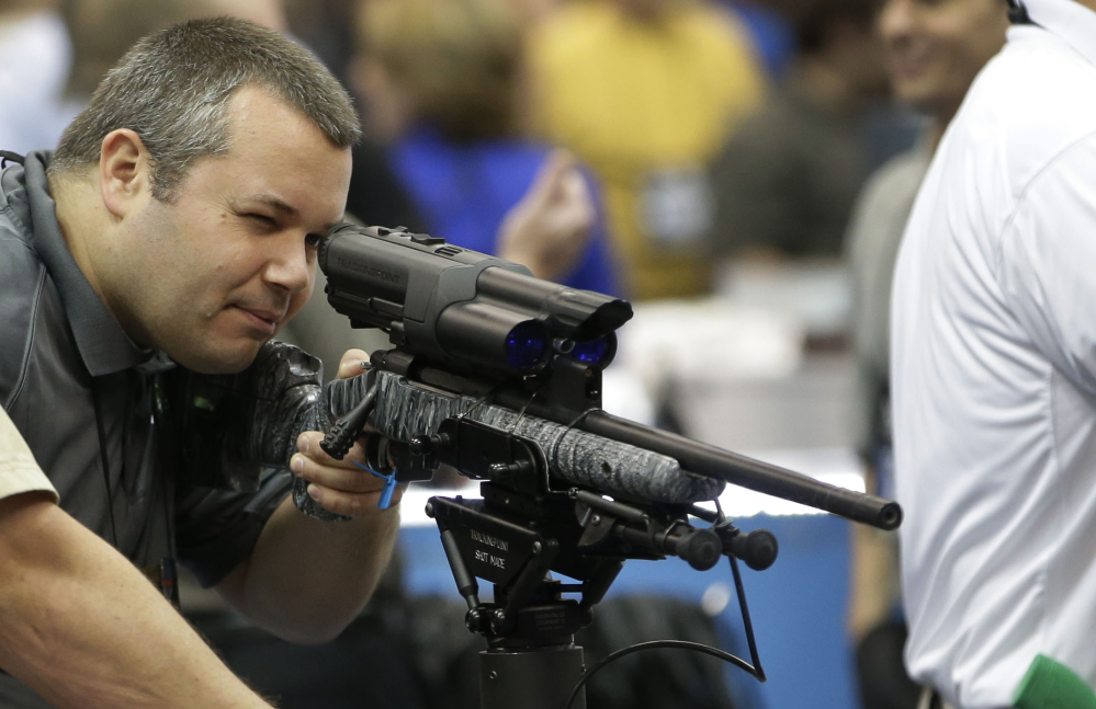 Mike Cisewski of Maple Plain, Minn., looks through a scope at the National Rifle Association's annual convention Friday at Lucas Oil Stadium in Indianapolis.