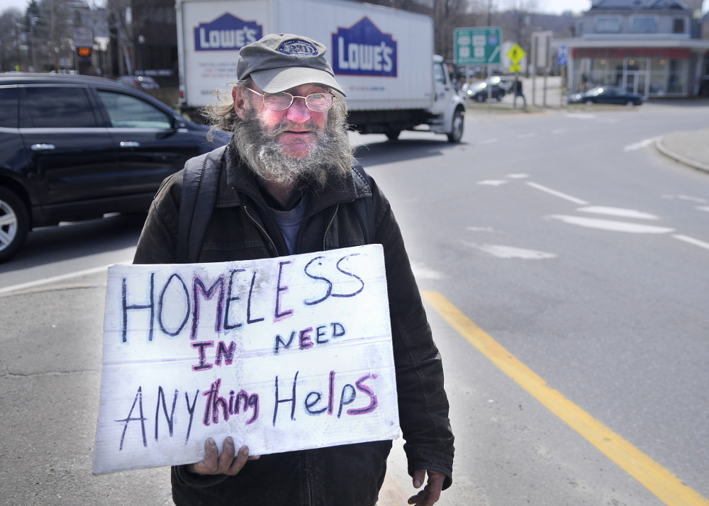 "PANHANDLING: Lloyd Bowden, 55, panhandles Friday at Memorial Circle in Augusta. Bowden said he is living in the basement of a relative's house in Augusta until he can buy a tent. He said the money people give him goes ""all to food."""