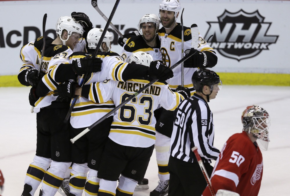 WIN AWAY: Detroit Red Wings goalie Jonas Gustavsson (50) skates by as the Boston Bruins celebrate their 3-2 overtime win in Game 4 against the Detroit Red Wings on Thursday in Detroit. The Bruins have a 3-1 series lead.