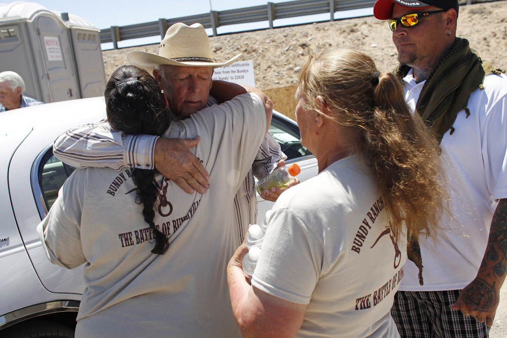 Rancher Cliven Bundy, second from left, hugs a supporter before holding a news conference near Bunkerville, Nev., on Thursday.