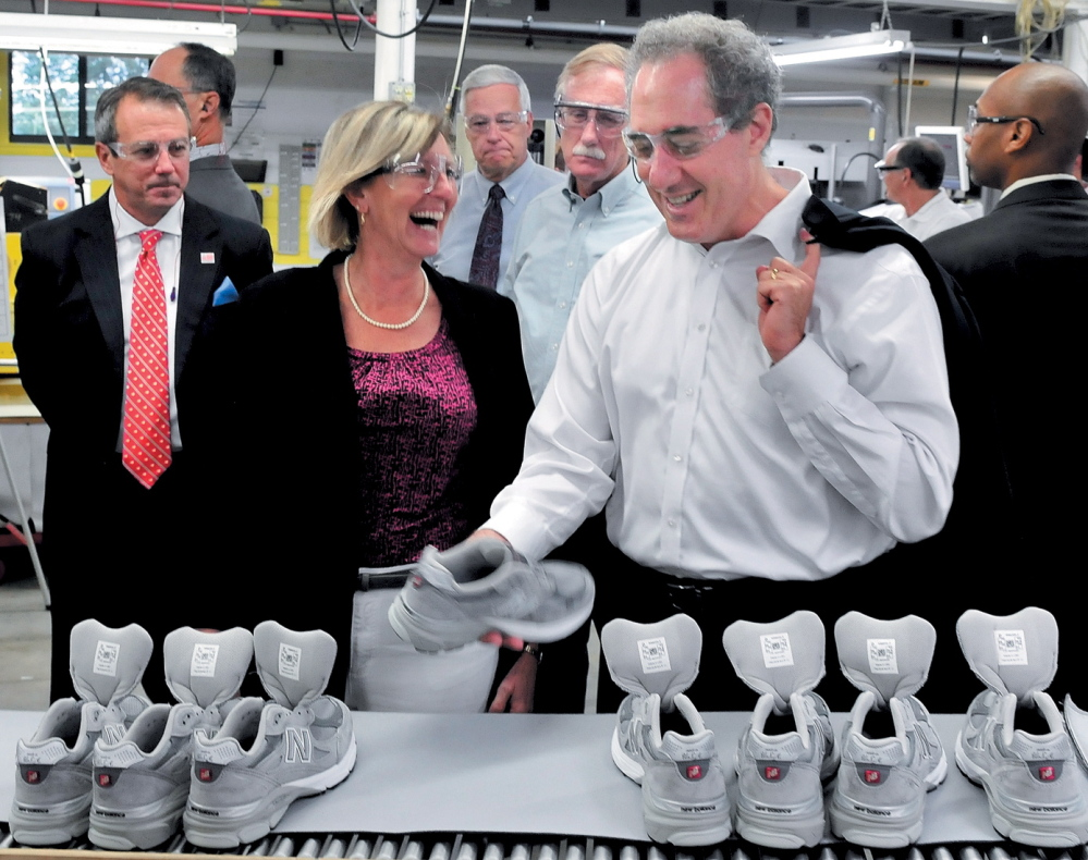 NICE FIT: U.S. Trade Representative Michael Froman, right, examines a sneaker at the New Balance company in Norridgewock during a tour in July. Company CEO Rob DeMartini, left, plant manager Raye Wentworth, U.S. Rep. Mike Michaud and U.S. Sen. Angus King Jr. also went on the tour.