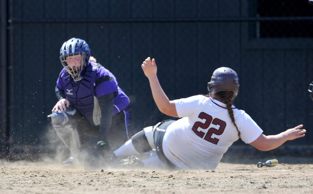 Staff photo by Michael G. Seamans Maine Central Institute's Paige Topel, 22, slides safely in to home plate as Waterville Senior High School catcher Kaitlyn Spaulding, 14, is late with the tag in Waterville.