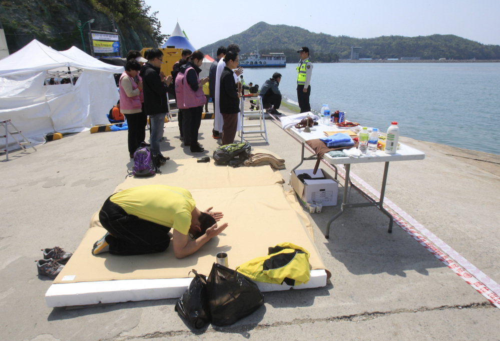 A relative of a passenger aboard the sunken ferry Sewol prays as he waits for news on his missing loved one at a port in Jindo, South Korea, Friday.