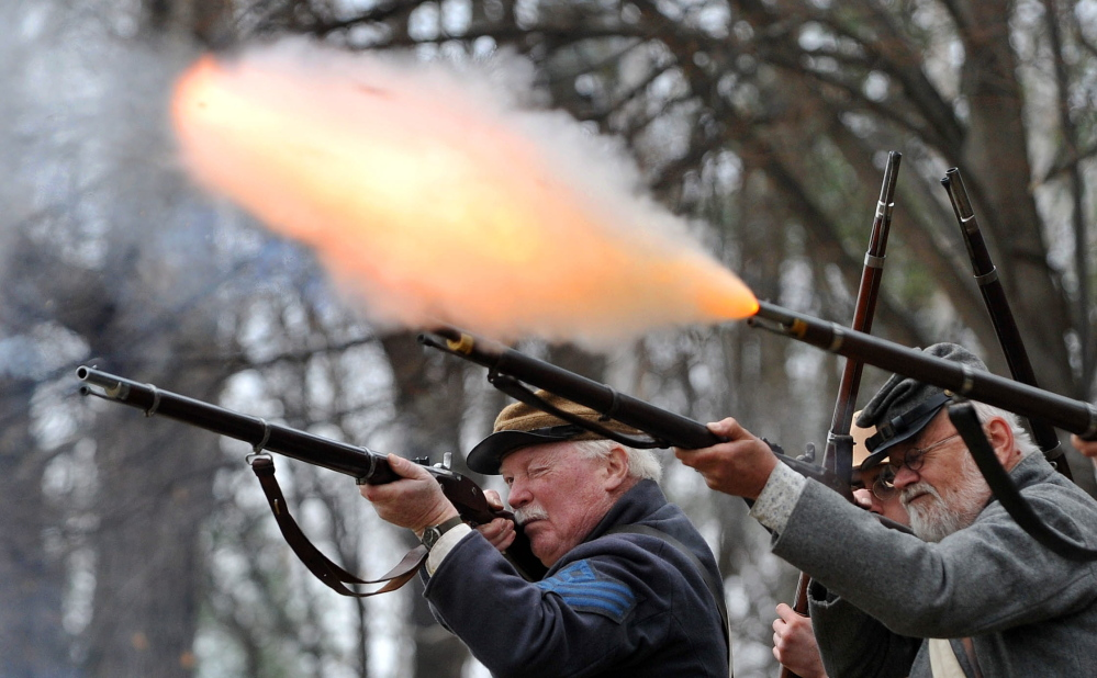 ALL FIRED UP: Members of the Confederate Army's 15th Alabama Company perform a firing demonstration Saturday during a Civil War re-enactment at Abbott Park in Farmington.