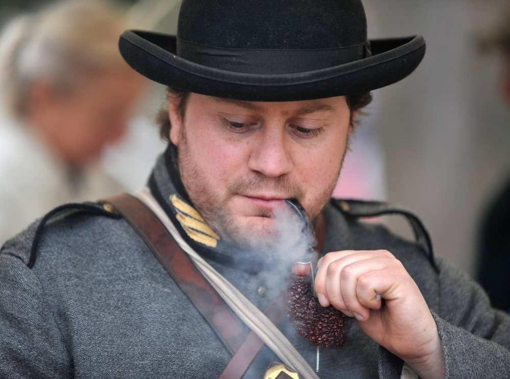 IN CHARACTER: Dave Laiche, captain of 15th Alabama Company, smokes a vintage pipe Saturday during a Civil War re-enactment at Abbott Park in Farmington.