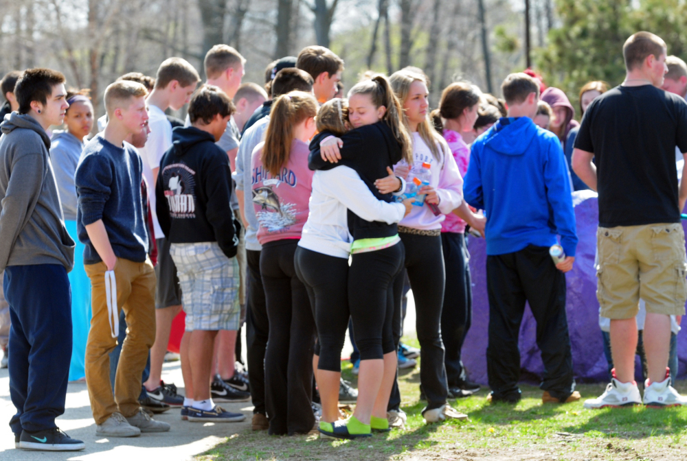 Students hug and spray paint a rock purple outside Jonathan Law High School in Milford, Conn., Friday.